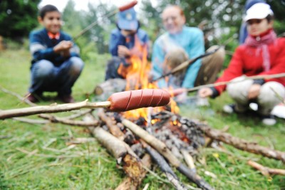 Gruppe grillend am Lagerfeuer