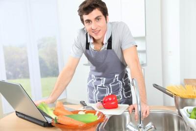 Koch mit Laptop in der Küche