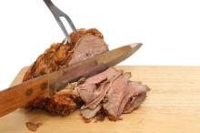 Braten, geschnitten mit Tranchiermesser und Fleischgabel