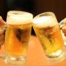 Zwei Biergläser beim Anstoßen